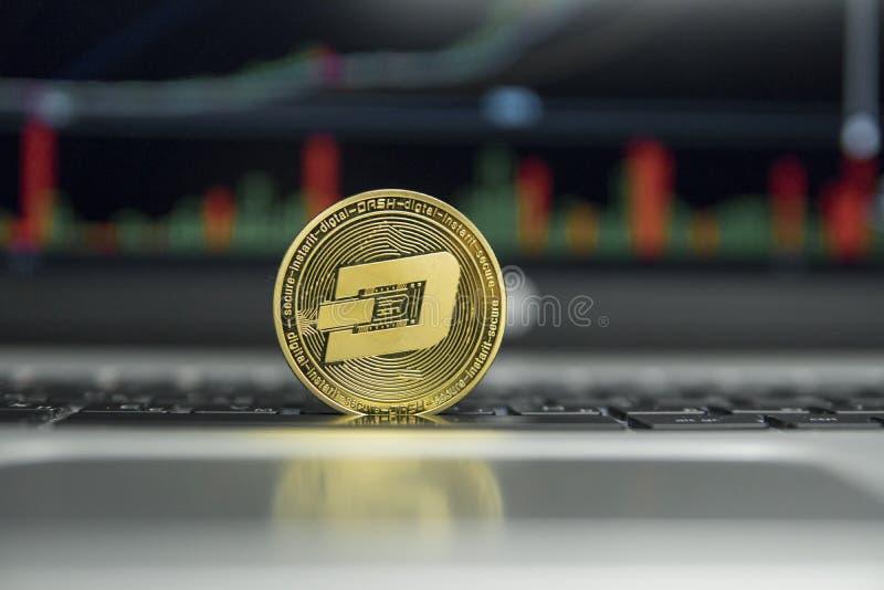 在银色膝上型计算机一个黑键盘的金黄破折号硬币和图绘制在屏幕上的图表图表作为背景 虚拟 库存照片