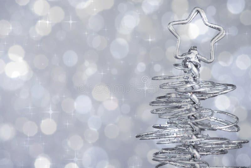 在银色色彩光bokeh背景, xmas假日的金属现代圣诞树 免版税库存照片