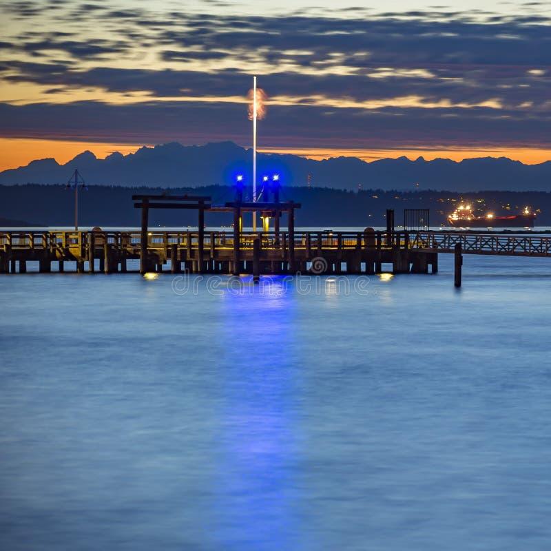 在银色镇静海洋的塔科马码头日落的 免版税库存图片