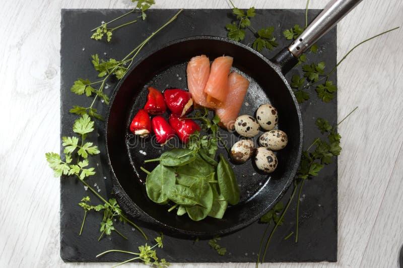 在铸铁煎锅的能转化为酮的食物用鹌鹑蛋意大利辣味香肠奶油奶酪菠菜和在板岩和白色的熏制鲑鱼求爱 免版税库存照片