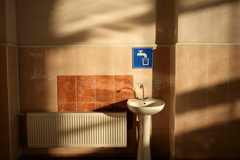 在铺磁砖的墙壁附近的白色水槽和蓝色轻拍在火车站一个等待的大厅里签字 免版税库存图片