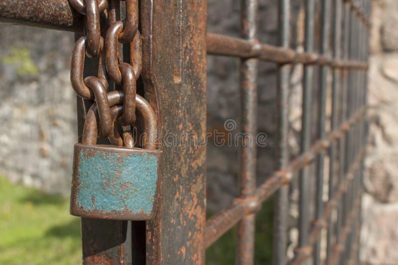 在链子的锁 与一把锁的老生锈的链子在铁门 标志监禁和奴隶制 库存照片