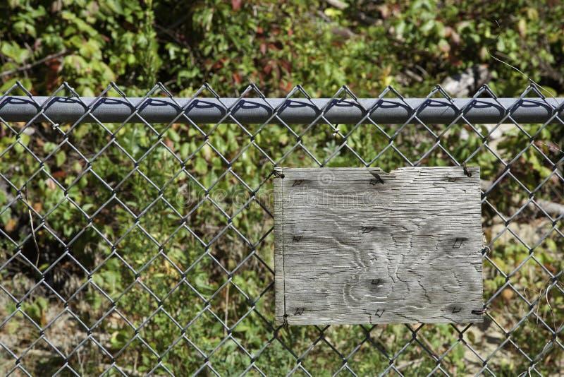 在链节篱芭的空白的土气木标志 免版税库存图片