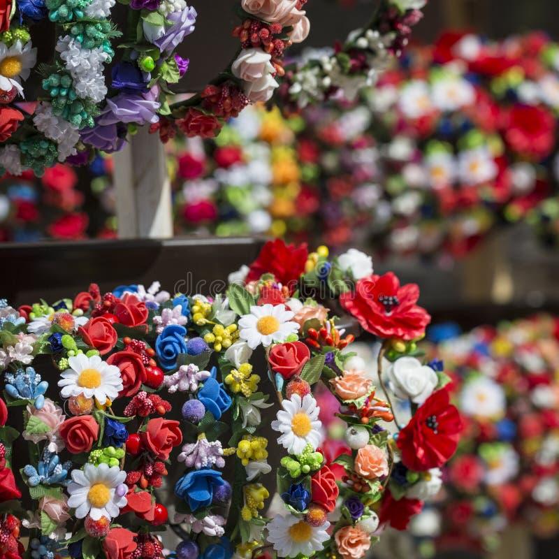在销售中的五颜六色的传统花花圈在地方市场上 图库摄影