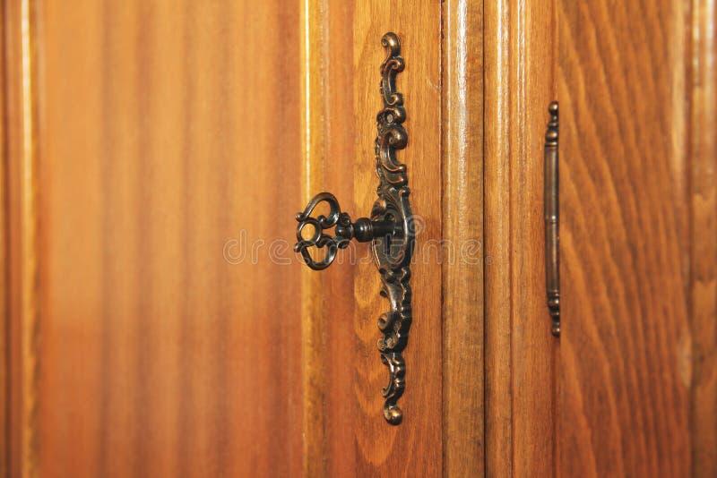 在锁的老古色古香的钥匙 木家具 免版税图库摄影