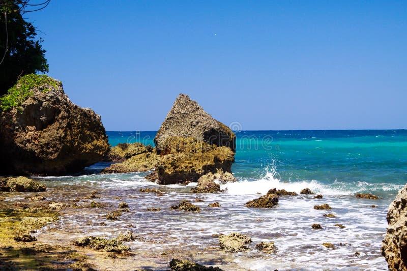 在锋利的岩石之外的看法在有波浪破碎机和强的海浪的-蓝色盐水湖,波特兰,牙买加绿松石风大浪急的海面 库存照片