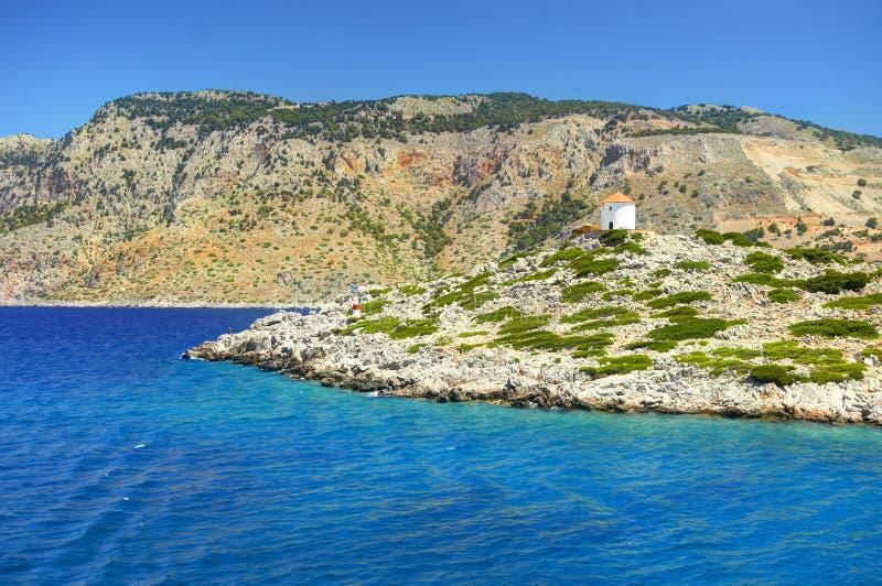 在锡米岛海岛石头的美丽的景色晃动与橙色屋顶的白色磨房撒粉于磨房在青山 Aeg蓝色透明的水  免版税库存图片