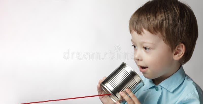 在锡罐电话的愉快的男孩戏剧,男孩附有了一个电话 免版税图库摄影
