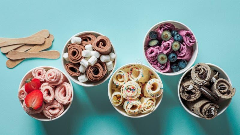 在锥体杯子的滚动的冰淇淋在蓝色背景 库存照片