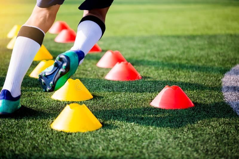 在锥体标志之间的足球运动员跑步和跃迁在绿色艺术 免版税库存照片