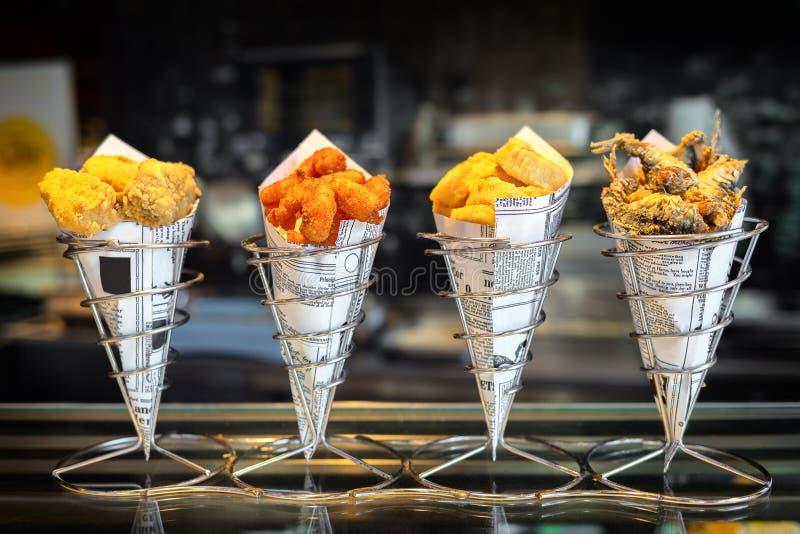 """在锥体的海鲜在柜台在西班牙与混杂的外带的烤鱼和油煎的海鲜的â€的smal街道商店""""快餐 库存图片"""