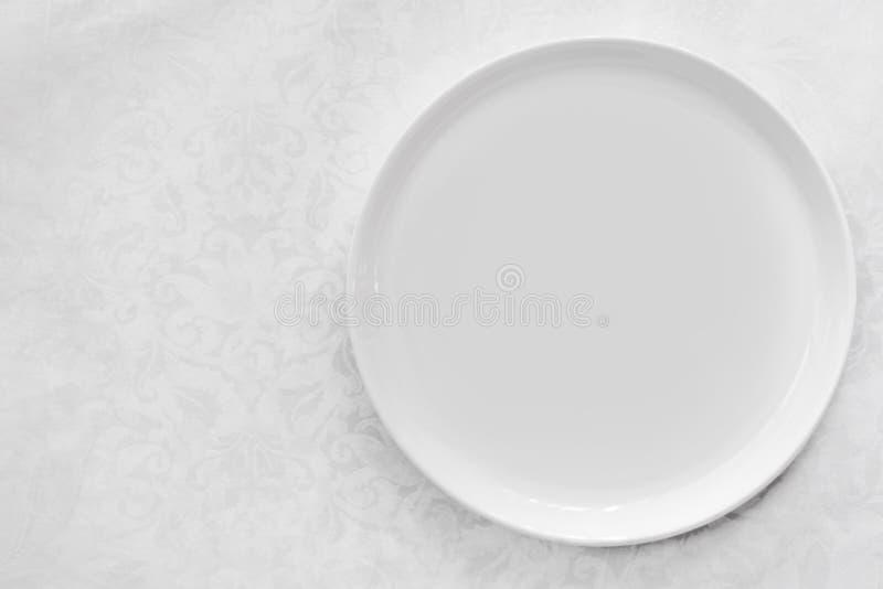 在锦桌布顶视图的空的白色板材 图库摄影