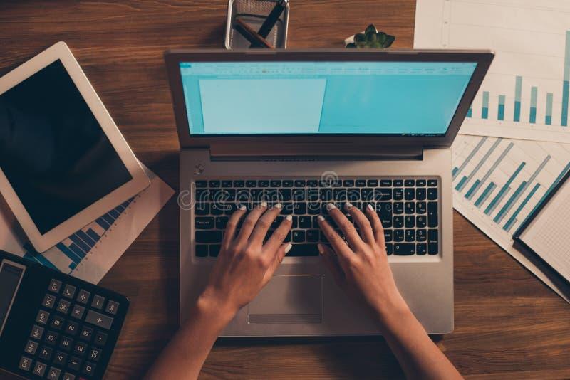在键入电子邮件伙伴人的新闻事业的女性手上大角度看法的播种的上面兼职自由职业者定货 图库摄影
