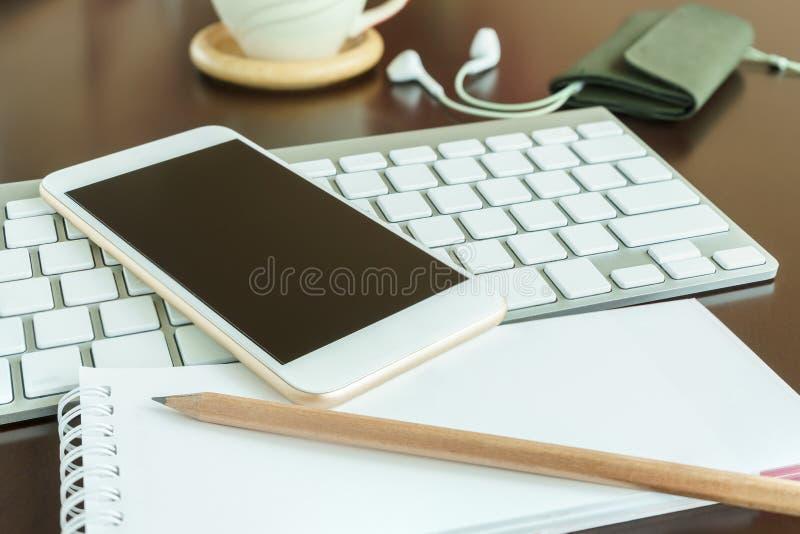 在键盘和笔记薄的巧妙的电话与铅笔 免版税图库摄影