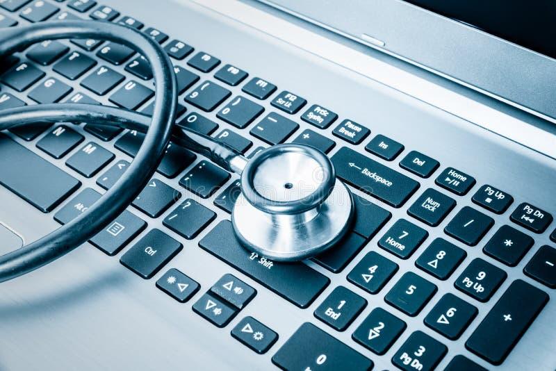 在键盘的听诊器在蓝色定了调子 免版税图库摄影