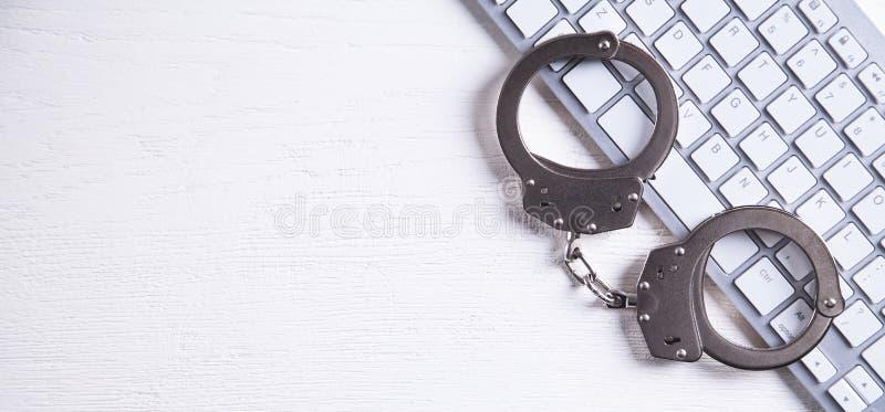 在键盘的手铐 网络罪行和网上欺骗的概念 免版税库存照片