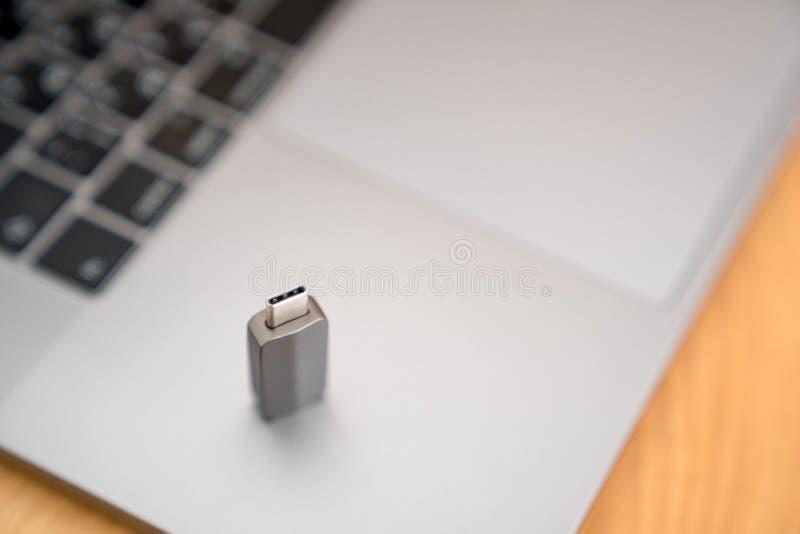 在键盘的灰色雷电USB-C适配器 免版税图库摄影