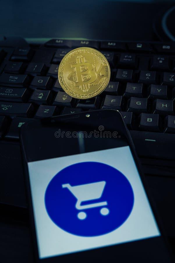 在键盘的Bitcoin和在智能手机的一个手推车标志 免版税库存照片