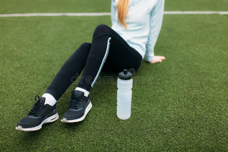 在锻炼以后的女孩,在橄榄球场的饮用水 美丽的女孩画象运动服的 图库摄影