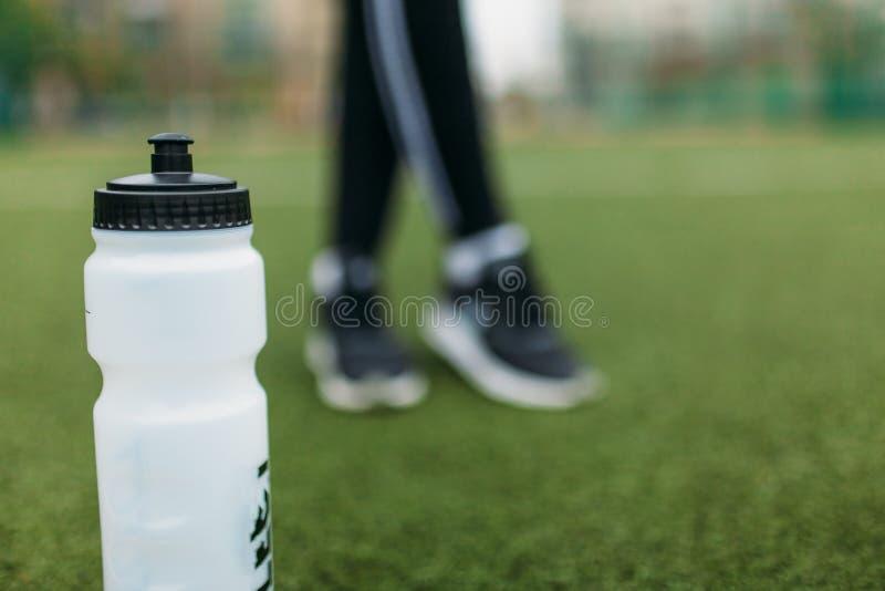 在锻炼以后的女孩,在橄榄球场的饮用水 美丽的女孩画象运动服的 免版税库存图片