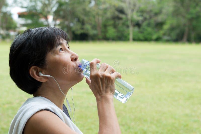 在锻炼以后的运动员妇女饮用水 免版税库存照片