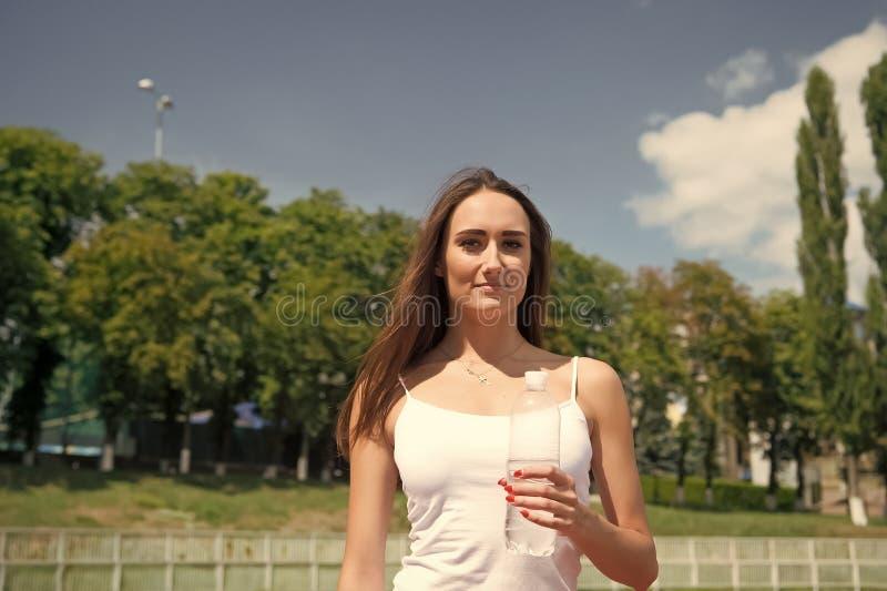 在锻炼期间,女孩对身体水合作用关心 渴妇女拿着水瓶 干渴和水分平衡概念 免版税库存图片