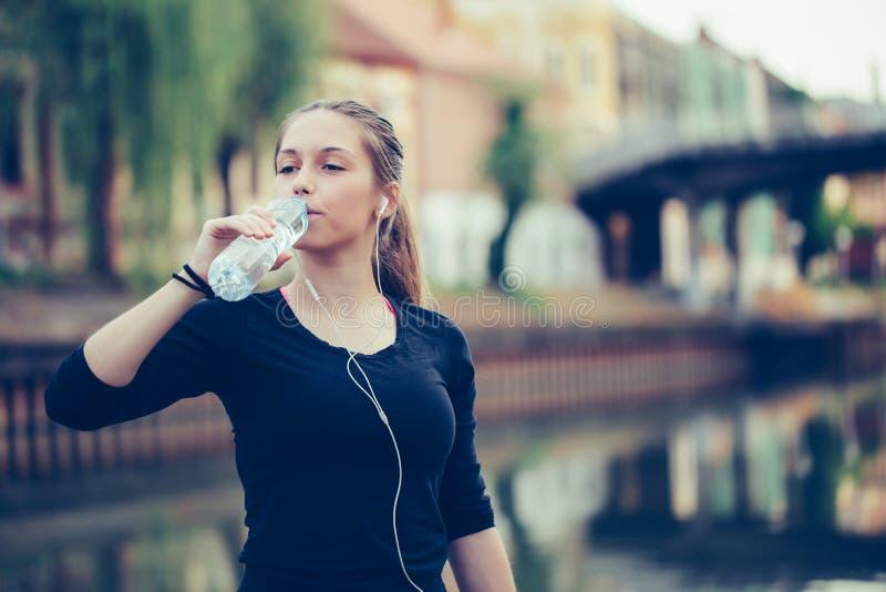 在锻炼行使以后的健身运动员妇女饮用水 免版税库存照片