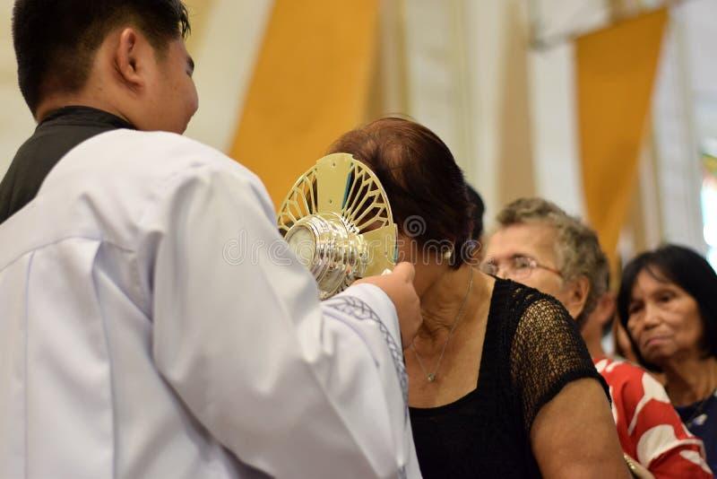 在镇庆祝期间,天主教妇女给亲吻的圣洁圣体匣的罕见的机会 免版税库存图片