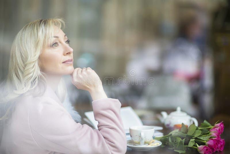 在镇附近的步行 桃红色的-蓝色口气金发碧眼的女人 城市咖啡馆 女性画象 库存照片