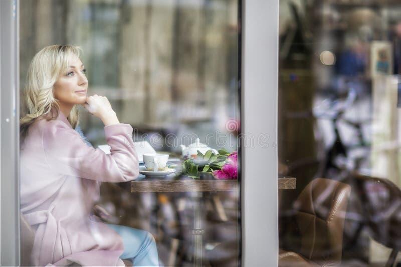 在镇附近的步行 桃红色的-蓝色口气金发碧眼的女人 城市咖啡馆 女性纵向 免版税图库摄影