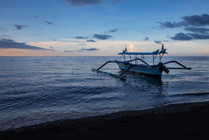 在镇静海洋和黑沙滩的蓝色小时与巴厘语小船 库存图片