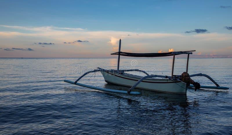 在镇静海洋和黑沙滩的蓝色小时与巴厘语小船 库存照片