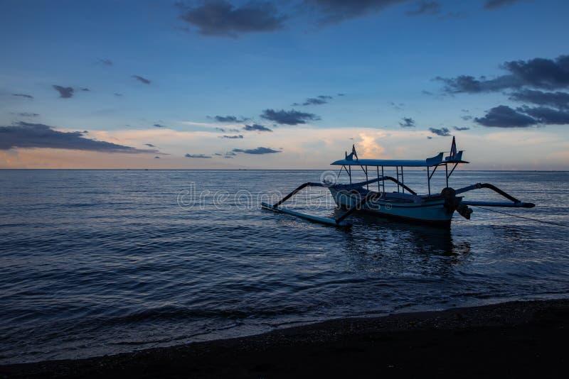 在镇静海洋和黑沙滩的蓝色小时与巴厘语小船 免版税库存图片