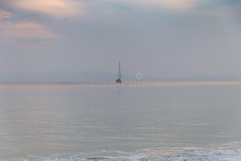 在镇静海洋的一条唯一风船 库存图片