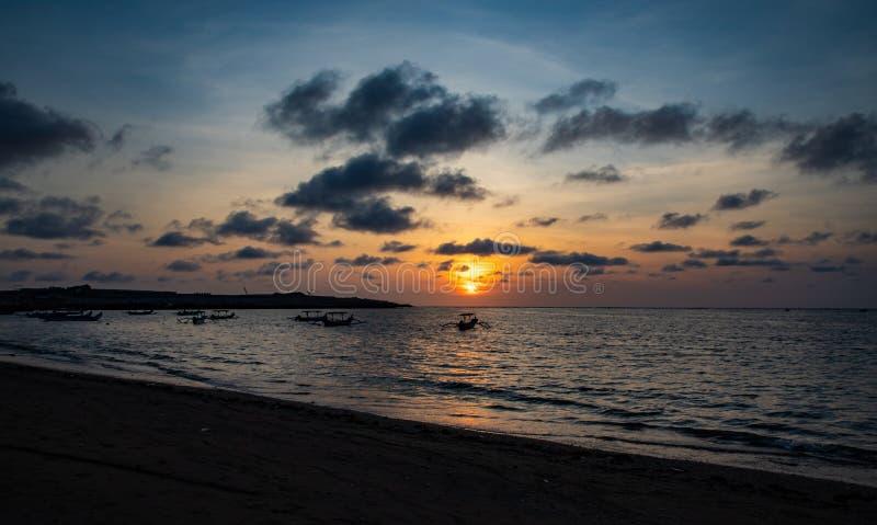 在镇静海洋的日落有巴厘语小船的 库存照片