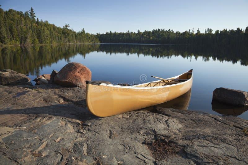 在镇静湖岩石岸的黄色独木舟有杉树的 免版税库存图片