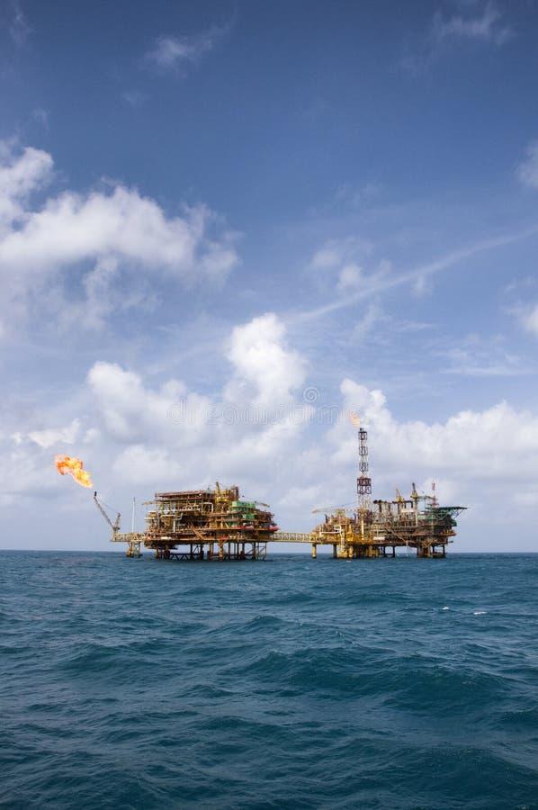 在镇静蓝色海的黄色抽油装置平台 免版税库存图片