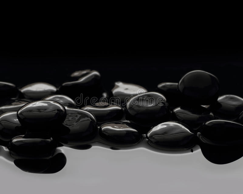 在镇静水的黑石头 免版税库存图片