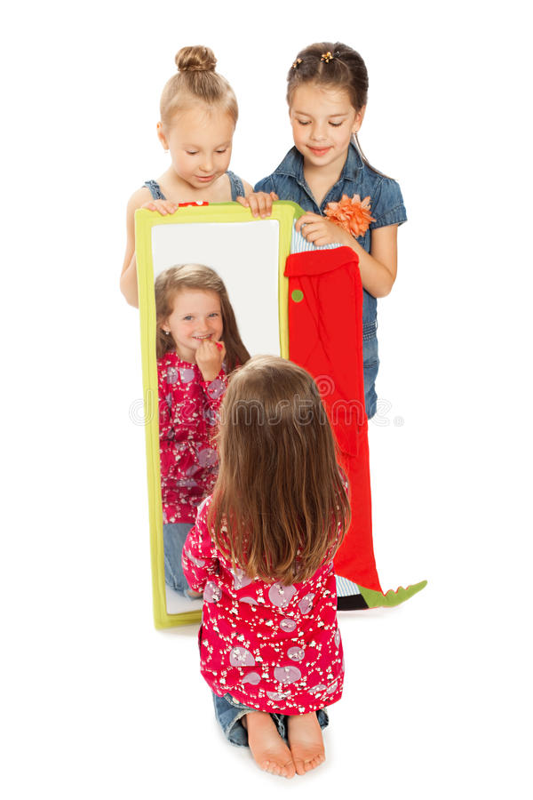 在镜子前面的快乐的女孩 图库摄影