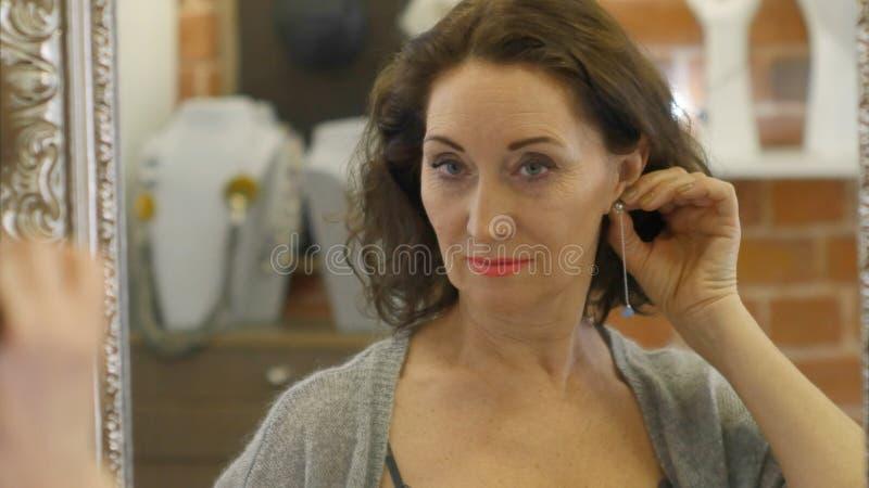 在镜子和微笑前面的妇女佩带的耳环的画象 库存图片