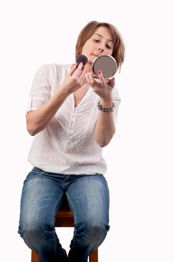 在镜子的有吸引力的少妇神色和申请脸红 免版税库存照片
