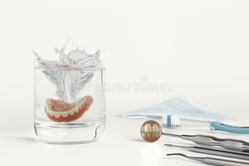 在镜子的牙在假牙旁边在水中 库存照片