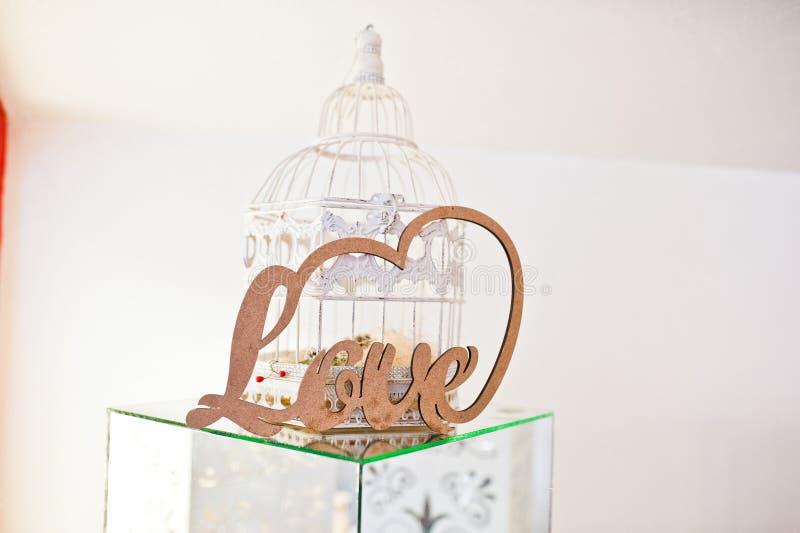 在镜子立方体和白色装饰笼子的木信件爱在weddin 免版税库存图片