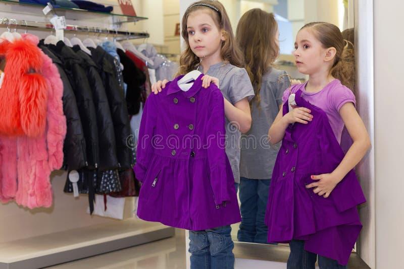 在镜子附近的两个小逗人喜爱的女孩试穿衣裳 库存图片