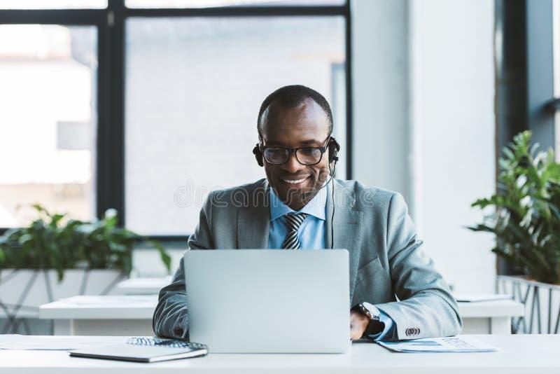 在镜片和耳机的微笑的非裔美国人的商人使用膝上型计算机 免版税图库摄影
