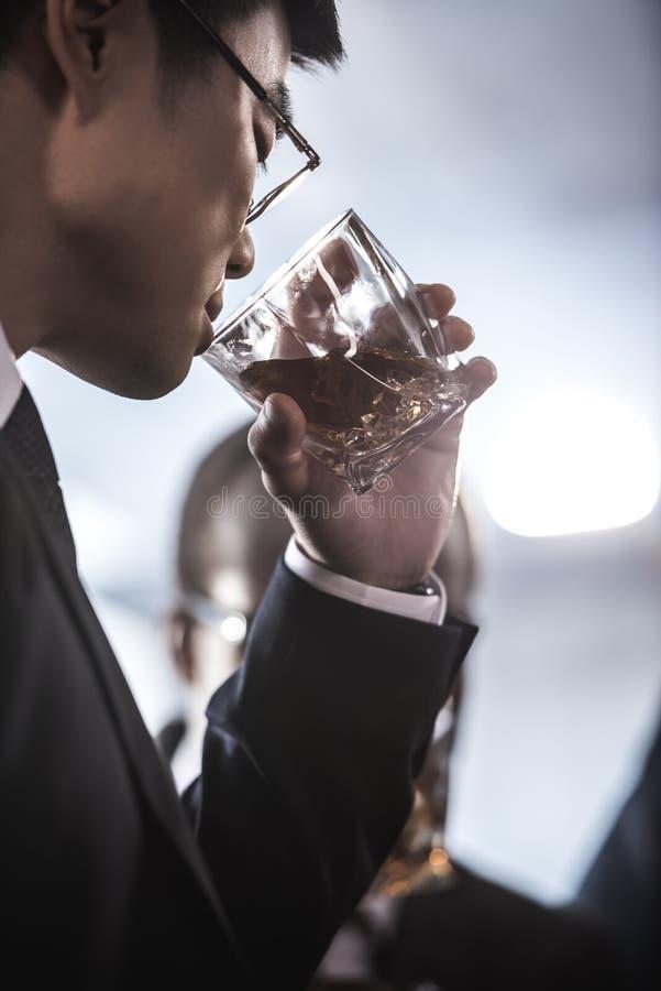 在镜片的亚洲商人喝从玻璃的威士忌酒 免版税库存照片
