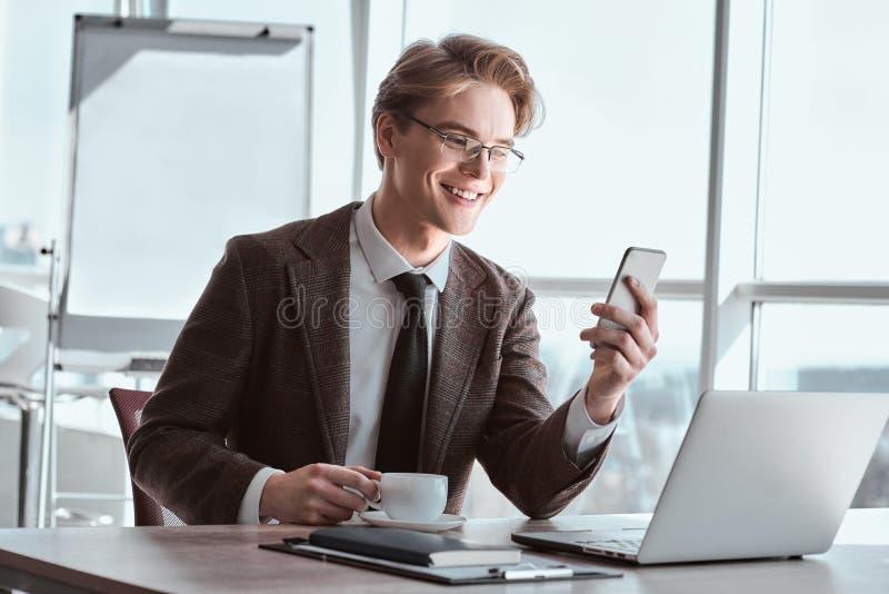 在镜片的年轻商人在办公室坐的饮用的coffe 免版税库存照片
