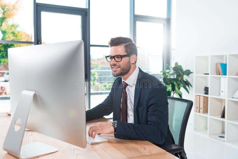 在镜片的微笑的年轻商人使用台式计算机 免版税库存图片