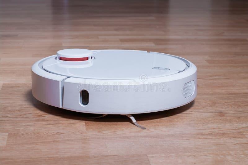 在镶花地板清洗的尘土的白色机器人吸尘器在屋子里 聪明机器人自动化无线清洁工艺 免版税库存图片