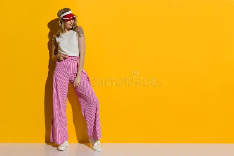 在镶边宽腿长裤和透明遮阳帘的微笑的时装模特儿在阳光下站立 免版税库存照片